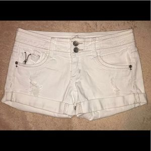 White jean shorts with rips.